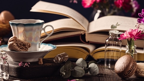coffee old books pink flowers and snacks
