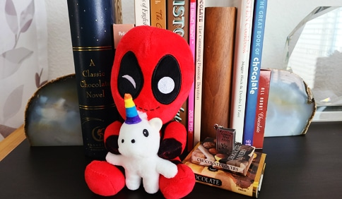 Deadpool holding rainbow unicorn plushie in front of many books about chocolate