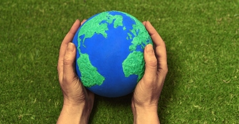 brown hands holding model of planet earth