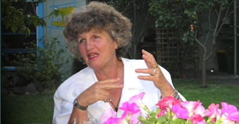 Joan Nestle speaking at table with flowers