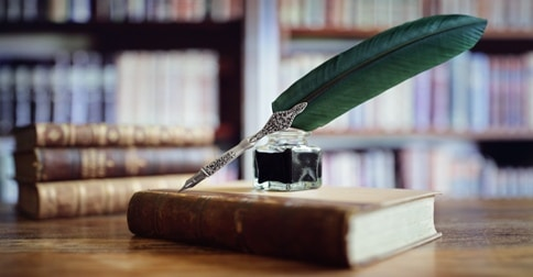 quill pen and ink well on old book in library