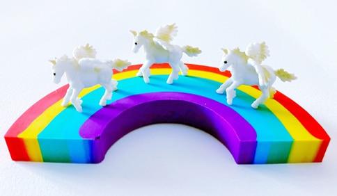 3 white unicorns on a rainbow